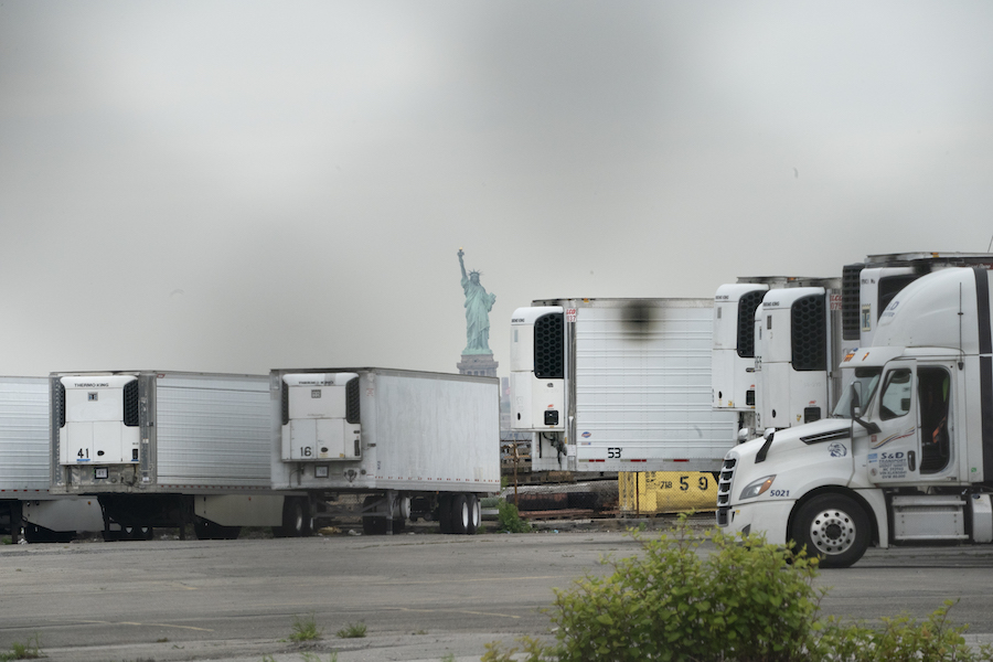 The Statue of Liberty pictured behind refrigeration trucks serving as a temporary morgue for victims of COVID
