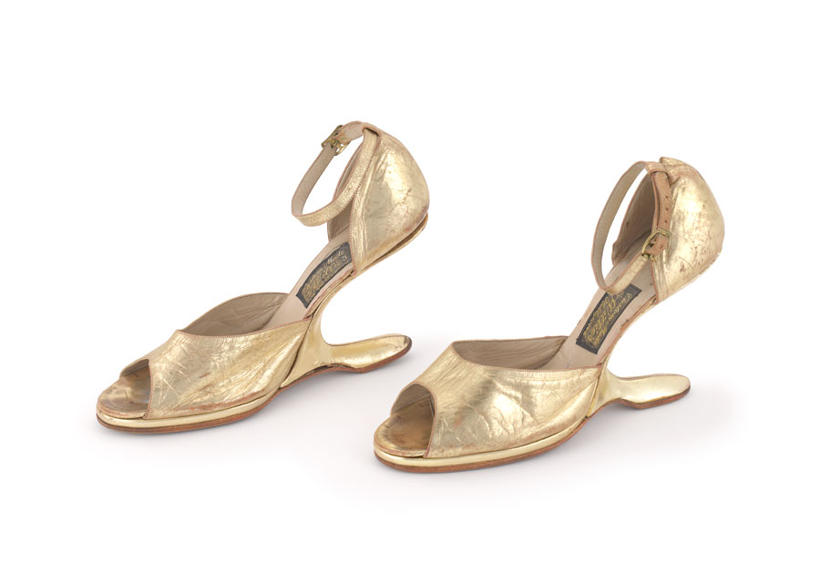 A pair of gold shoes, that are shaped like high heels. Rather than a heel, they have a piece that extends back from the base