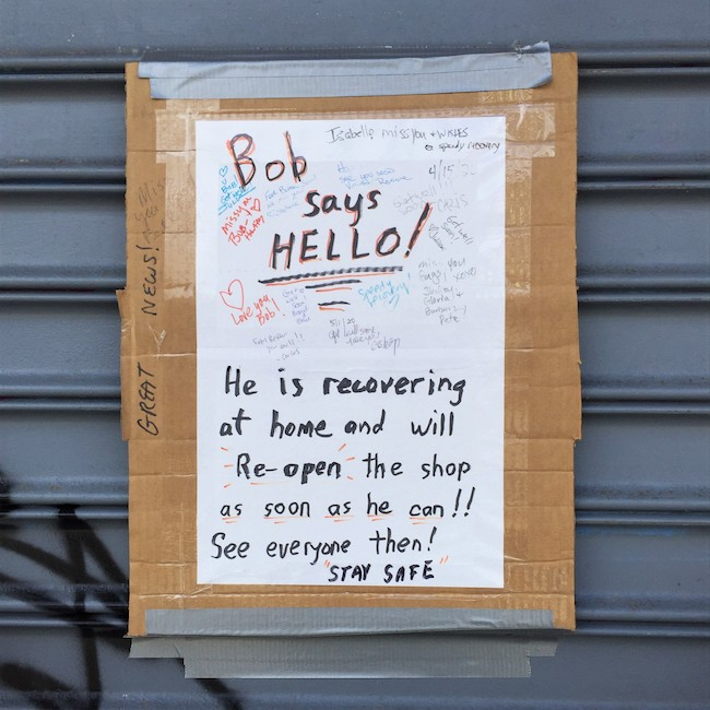 "Sign, written on white paper taped on to cardboard, is duct taped to the metal grate on a closed storefront. Sign reads ""Bob says Hello! He is recovering at home and will Re-open the shop as soon as he can!! See everyone then ! STAY SAFE. Small, personal messages from multiple people appear in the space around these words."