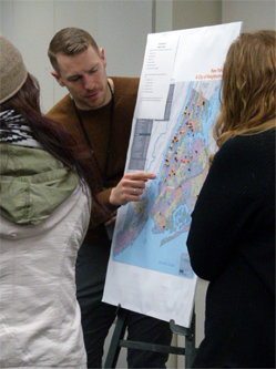 Participants discuss a map using different color pins and beads to show their borough of residence, length of commute, and workplace location to analyze commuting patterns.