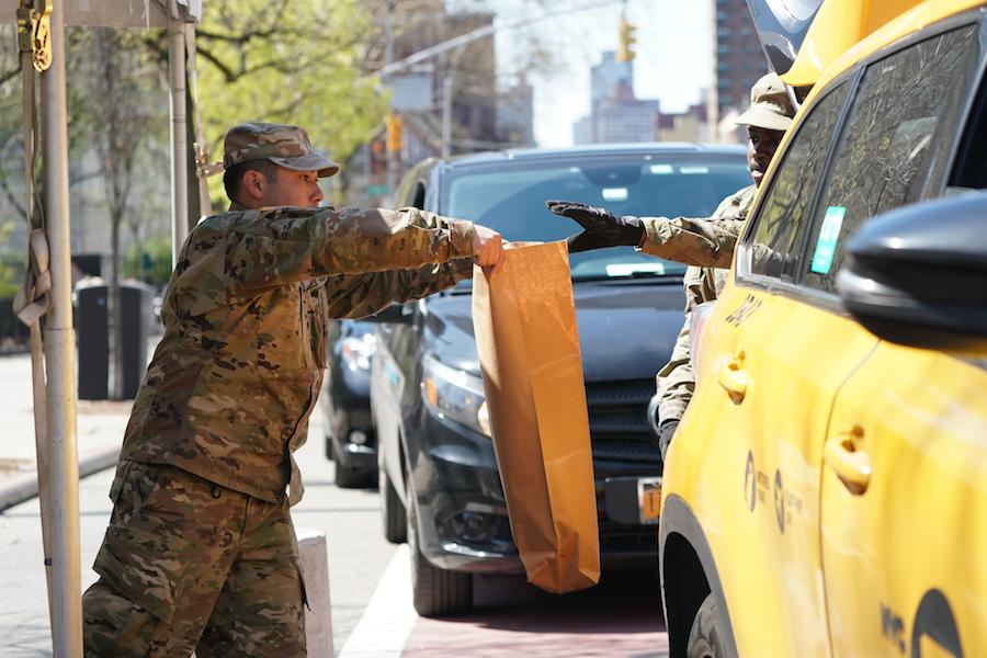 [Members of the U.S. Army National Guard distribute food in Harlem]