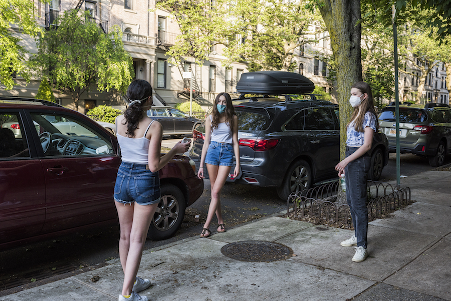 Three girls wearing masks stand apart but facing each other in a triangular fashion on the sidewalk in front of parked cars on a city side street