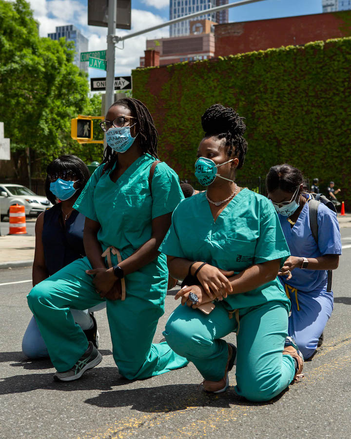 Four nurses in scrubs an masks kneel in a parking lot.