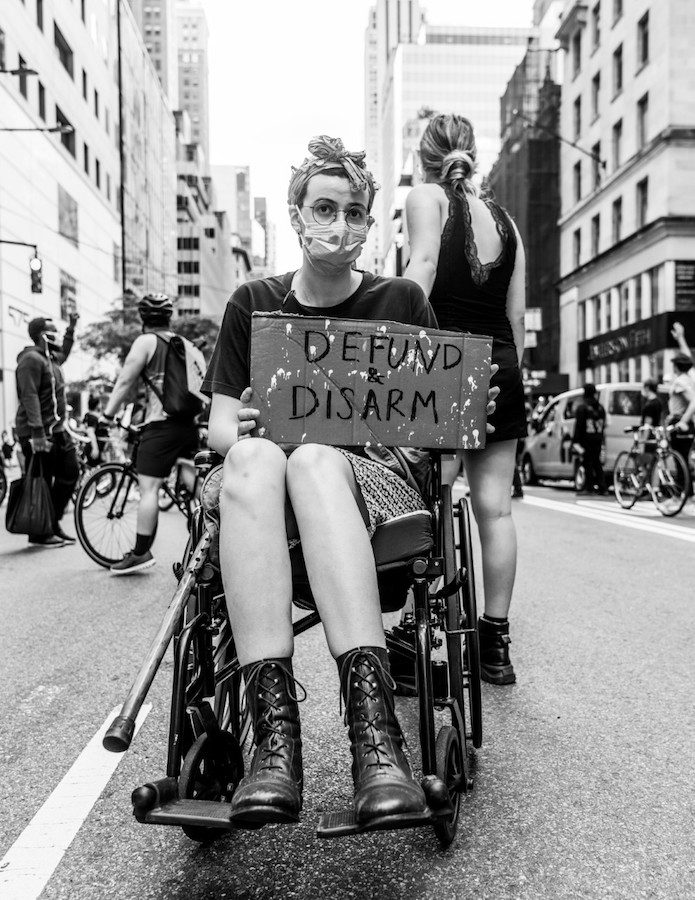 A woman in a wheelchair holds a sign at a protest.