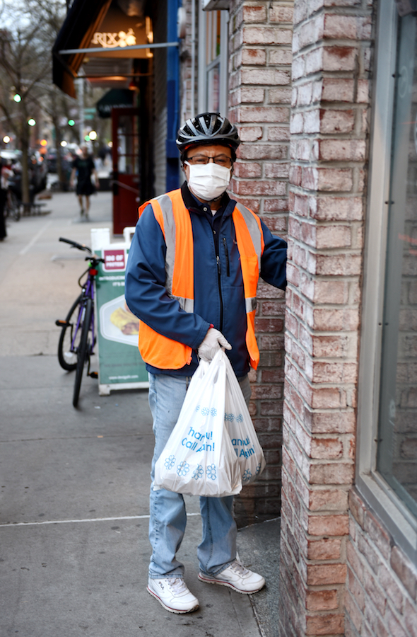 A delivery worker in a mask stands outside of a building.