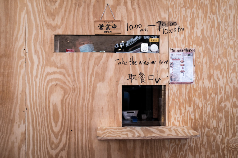 Plywood in front of a restaurant window, with small openings for take out and taking orders.