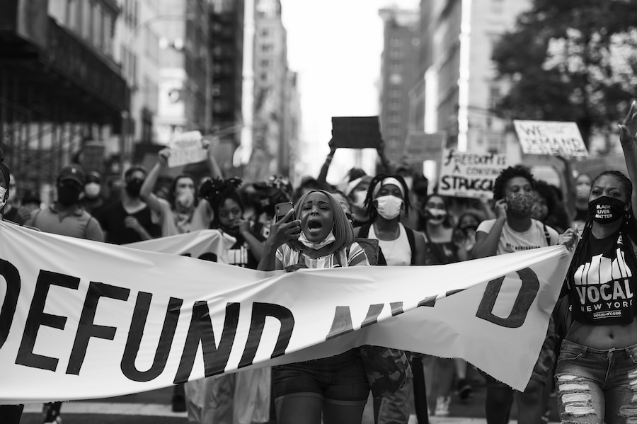 """A crowd of marchers hold a sign that reads """"DEFUND NYPD"""""""