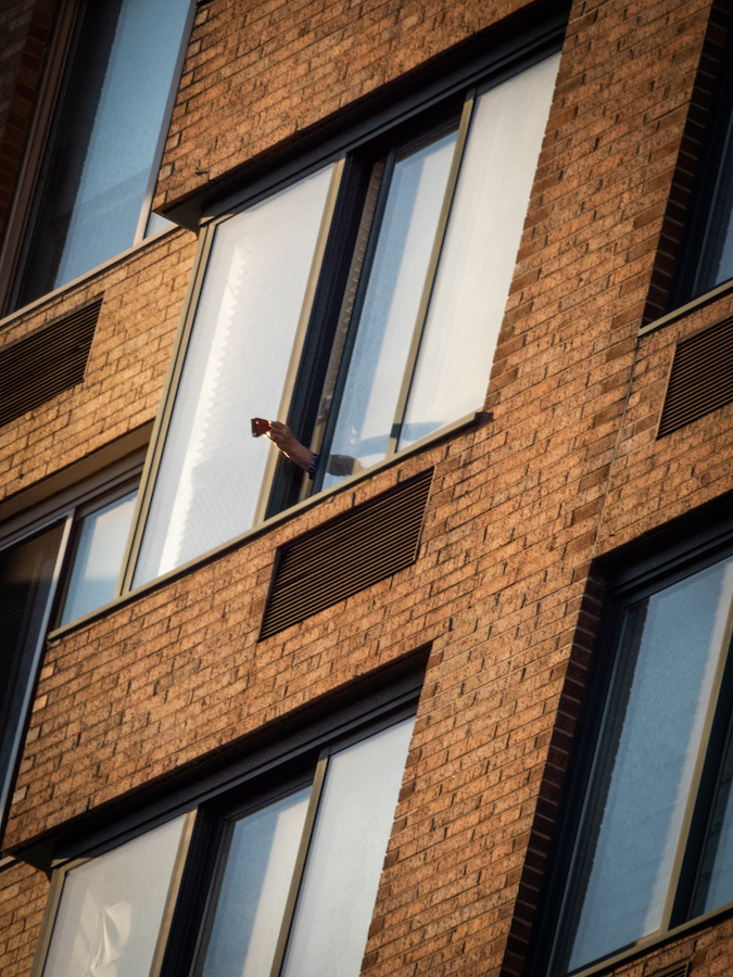 """Someone holds a clapper outside an apartment window as part of the """"7pm salute"""" during the COVID-19 pandemic."""