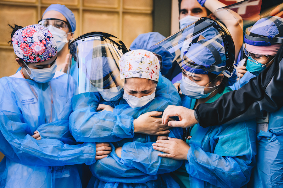 A group of medical workers stand holding each other wearing PPE including masks, face shields, and gowns.