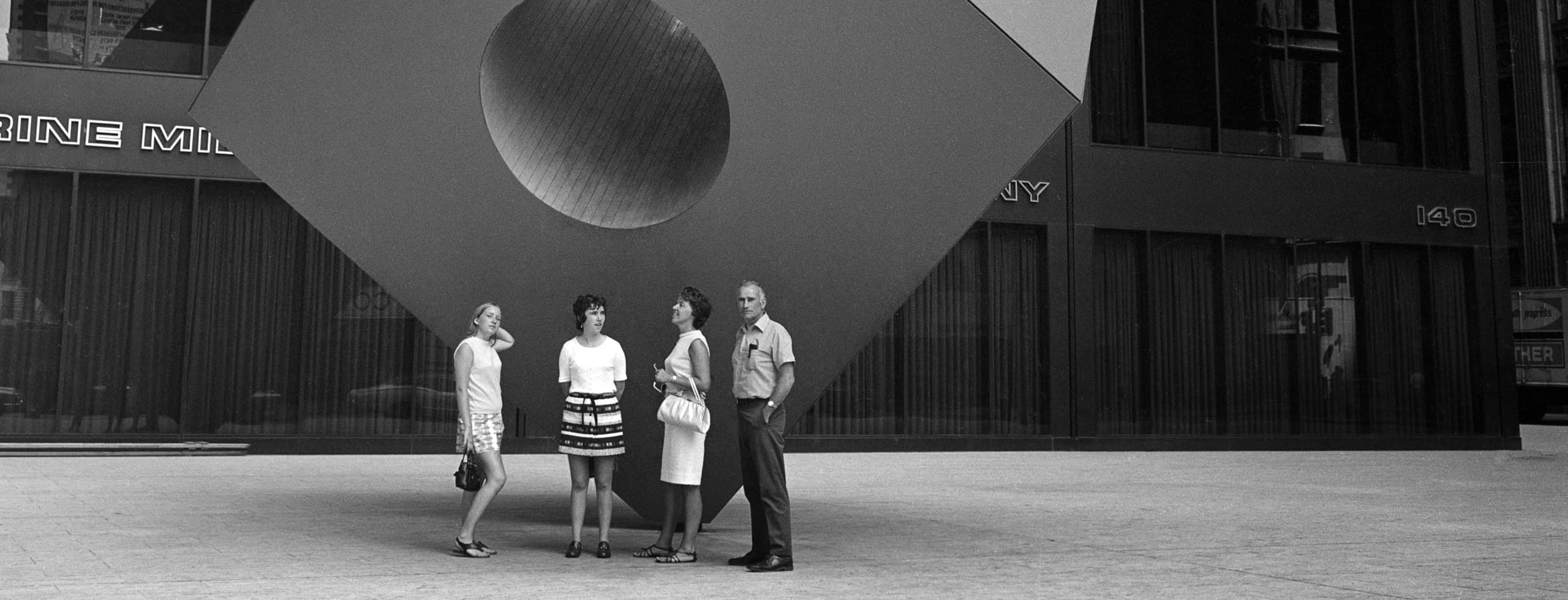 Four people stand on the sidewalk in front of a large statue of a cube with a hole going through the center of it