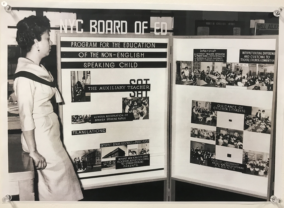 A woman stands in front of a Recruitment Board for Spanish-speaking Substitute Auxiliary Teachers in New York City public schools.