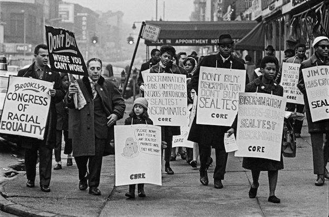 A black and white photograph of people from Brooklyn CORE walking with signs in a boycott against Sealtest Dairy Company in 1963