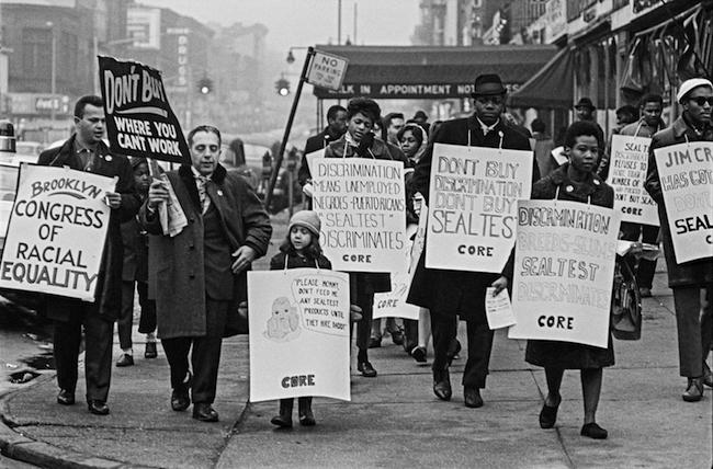 1963年にSealtestDairyCompanyに対してボイコットで看板を持って歩いているブルックリンCOREの人々の白黒写真