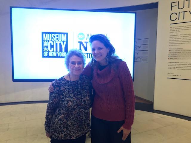 Dos mujeres se unen frente a una pantalla con los logotipos para el Día del Museo y la Historia.