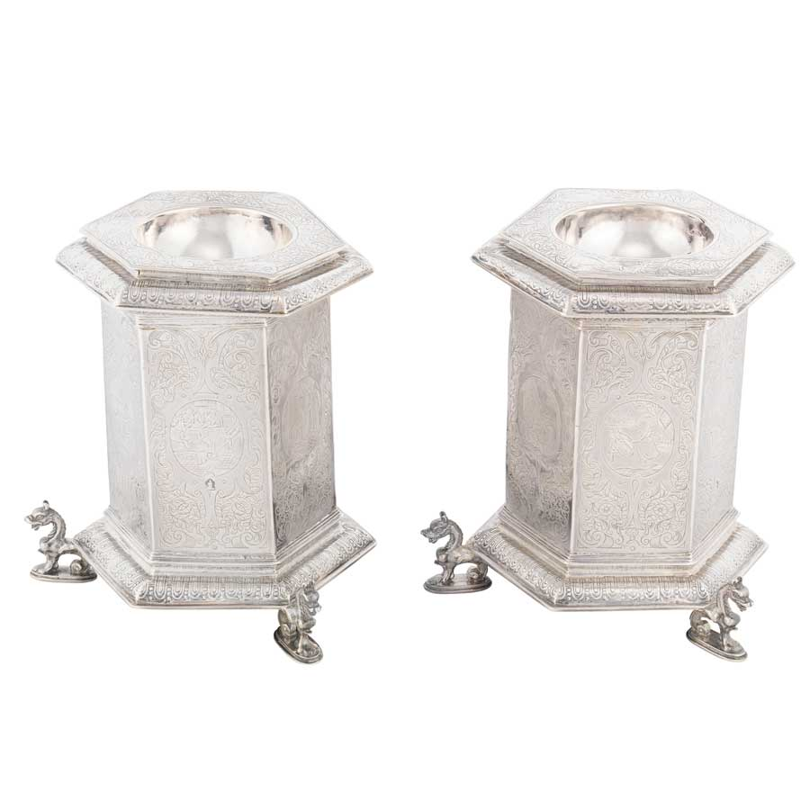 Two intricately detailed silver containers shaped like a hexagonal prism, with an indent at the top to hold salt