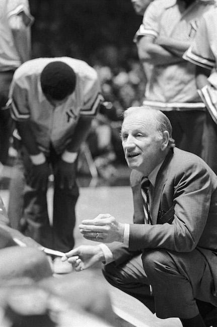 Imagem do técnico do Knicks, Red Holzman, ajoelhado e conversando com jogadores na quadra.