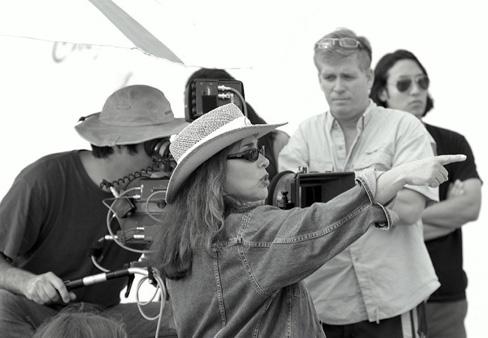 Una imagen en blanco y negro de la directora de cine Susan Seidelman sentada frente a una cámara con un grupo de 3 personas. Ella esta apuntando a la derecha