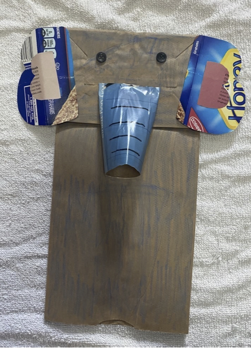 Sac à lunch en papier brun transformé en marionnette à main conçue pour ressembler à un éléphant. Il a deux boutons noirs pour les yeux, deux oreilles faites à partir d'un récipient en carton bleu et un tronc fait à partir d'un rouleau de papier toilette recouvert de papier magazine bleu.