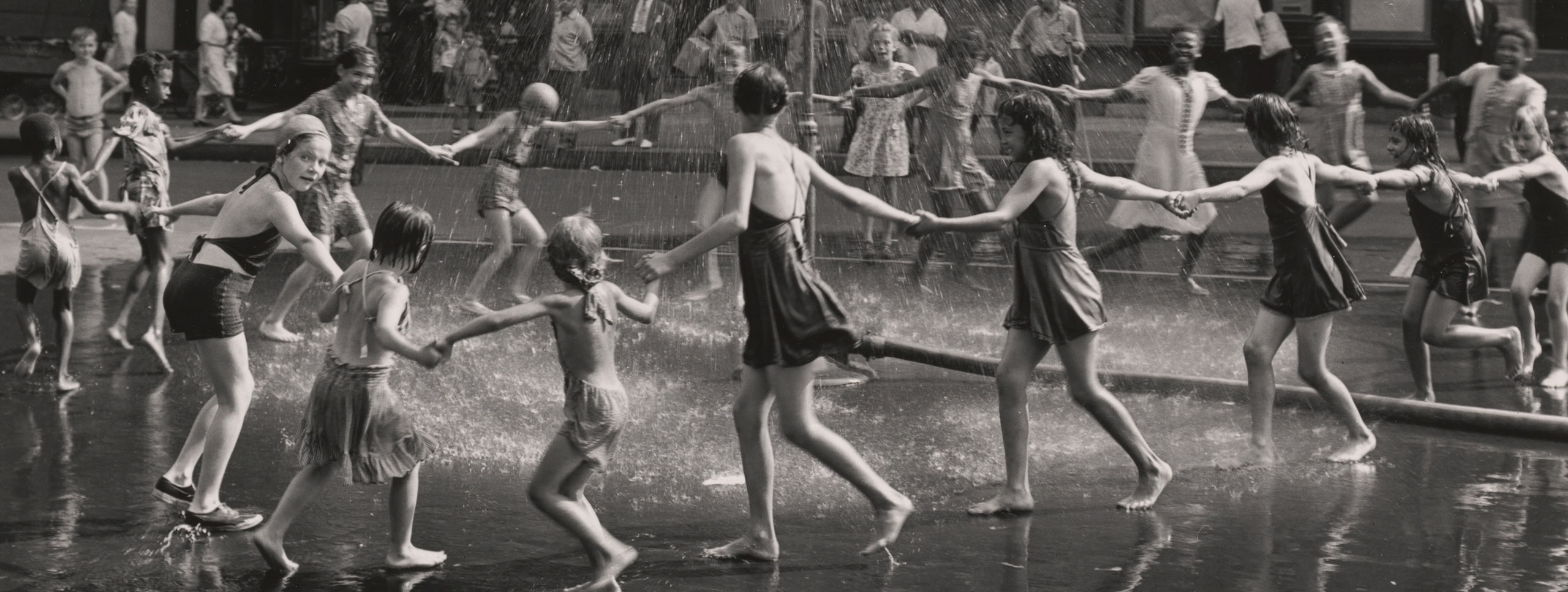 A group of children and teenagers hold hands in a circle as they run around a playground sprinkler