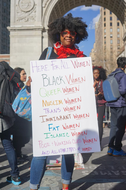 Woman holding a sign that reads: Here For All Women Black Women, Queer Women, Muslim Women, Trans Women, Immigrant Women, Fat Women, Islamic Women, Poor & Working Class Women, and all other types of Women.