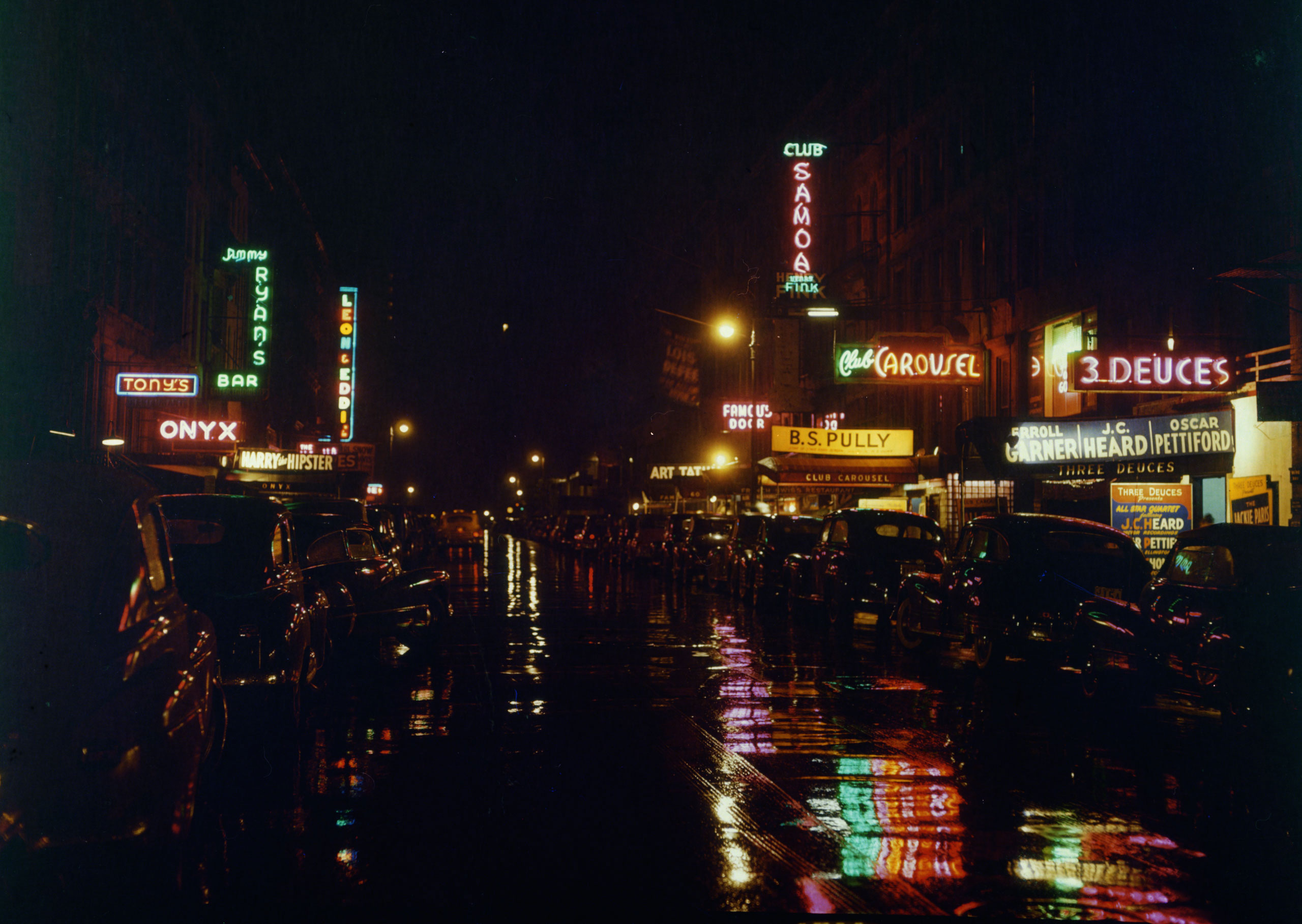 Road at nighttime, with neon signs reflecting on the wet pavement, and parked cars on either side of the street