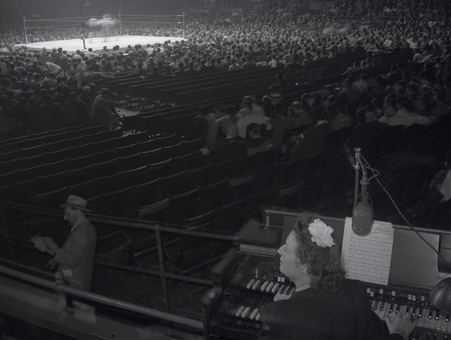 L'organiste des sports Gladys Gooding est assis à un orgue au Madison Square Garden avec un ring de boxe et un public à l'arrière-plan.