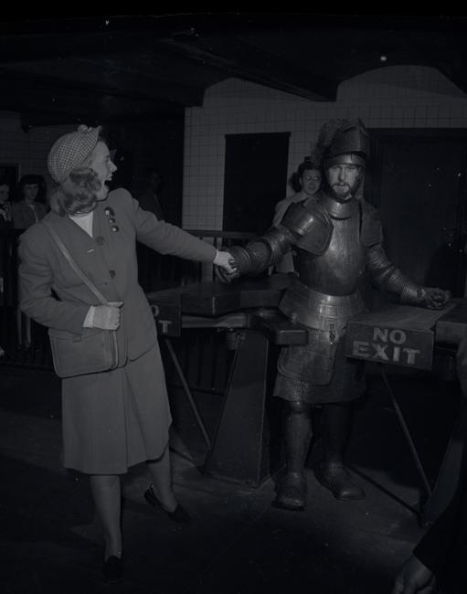Un homme en armure métallique traverse un tourniquet de métro tandis qu'une femme en costume lui tient la main et le guide.