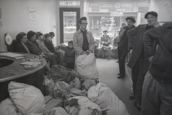 Plusieurs hommes et femmes se tiennent debout dans une laverie de Greenwich Village avec des sacs de lessive et des machines à laver devant eux.