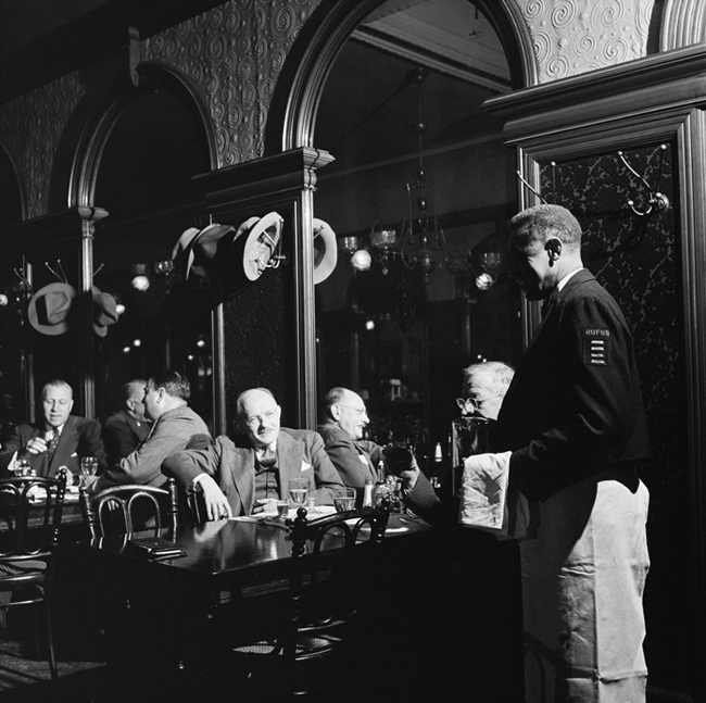 Interior of Gage and Tollner restaurant with men eating and waiter nearby.