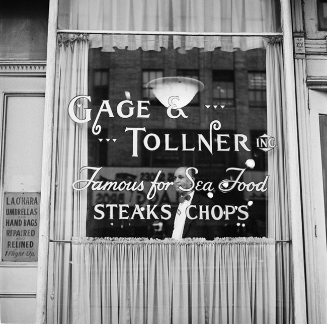 "Exterior of Gage and Tollner restaurant. The lettering on the window reads ""Gage & Tollner Inc. Famous for Sea Food, Steaks, Chops."" A waiter is visible through the window."