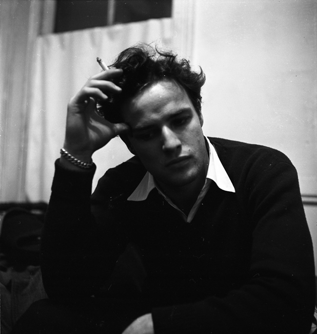 L'acteur Marlon Brando est assis à l'intérieur, portant un pull et tenant une cigarette.