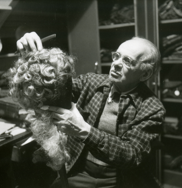 Un homme portant des lunettes tient devant lui une longue perruque bouclée appartenant au Metropolitan Opera.