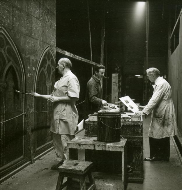 Trois hommes en blouses et tabliers tiennent des pinceaux et des papiers pendant qu'ils peignent des ensembles pour le Metropolitan Opera avec des tables de travail et des seaux de peinture à côté d'eux.