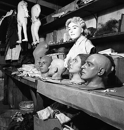 Wax heads and bodies sit on a workbench and are suspended from the ceiling of Hattie McKeever's workshop