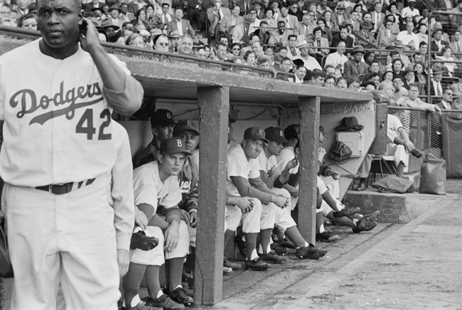 Jackie Robinson stands near the dugout during a game with the Brooklyn Dodgers