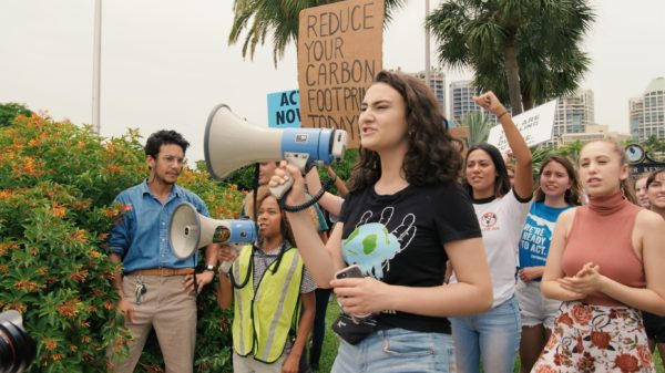"Jamie Margolin holds a blue and white bullhorn that she is actively speaking into. A crowd of youths follows behind her shouting and holding signs that read ""Reduce your carbon footprint today."""