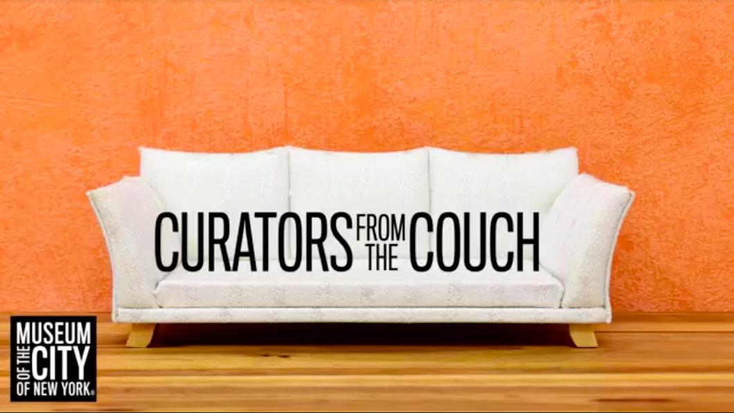 """오렌지 페인트 벽과 나무 바닥에 흰색 소파. 소파의 텍스트는 """"카우치의 큐레이터""""를 검은 색 글자로 읽습니다."""