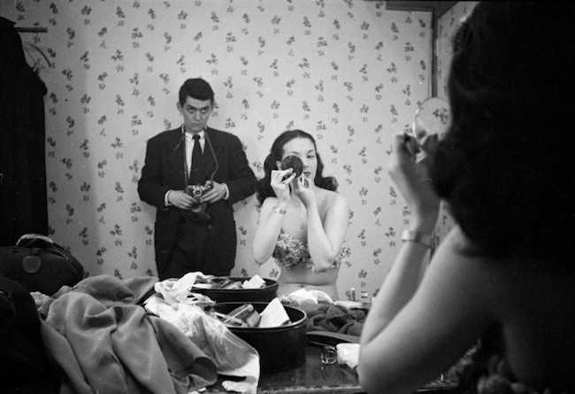 A woman sits at a mirror in costume, putting on make-up for a performance. A man stands against the wall with a camera.