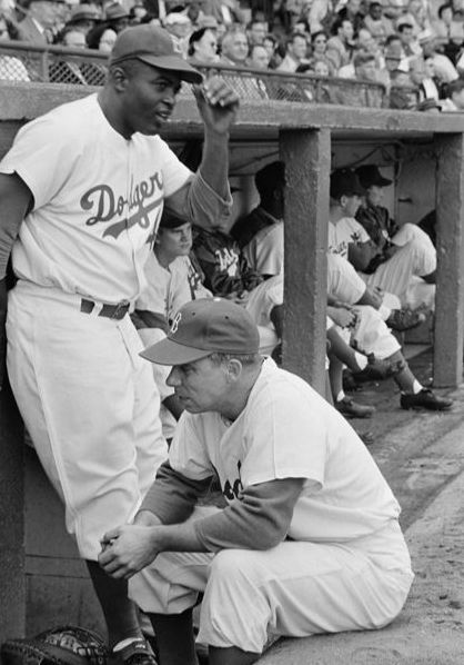 Jackie Robinson leans against the Dodgers' dugout while talking to captain Pee Wee Reese