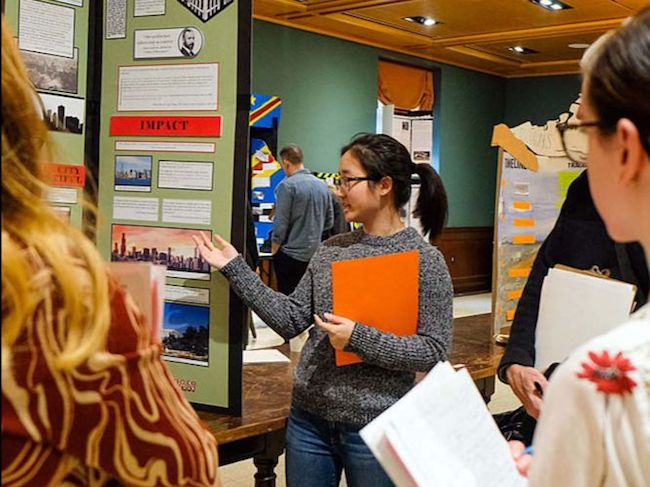 A student stands in front of her History Day project display.