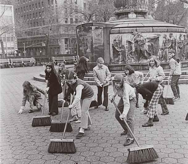 Black and white photo of a group of girls sweeping sidewalks in NYC on Earth Day.