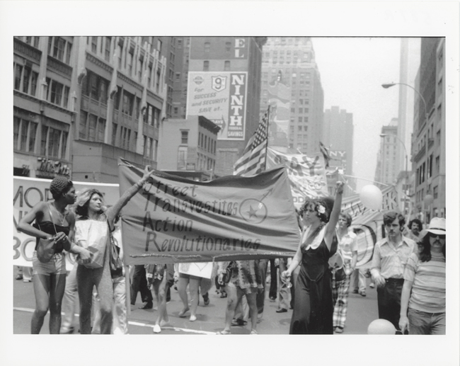 Black and white photograph featuring a parade during Christopher Street Liberation Day. Three figures, in front hold a banner for STAR, or Street Transvestite Action Revolutionaries.