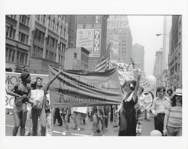 Fotografía en blanco y negro con un desfile durante el Día de la Liberación de Christopher Street. Tres figuras, en el frente, sostienen una pancarta para STAR, o Street Transvestite Action Revolutionaries.
