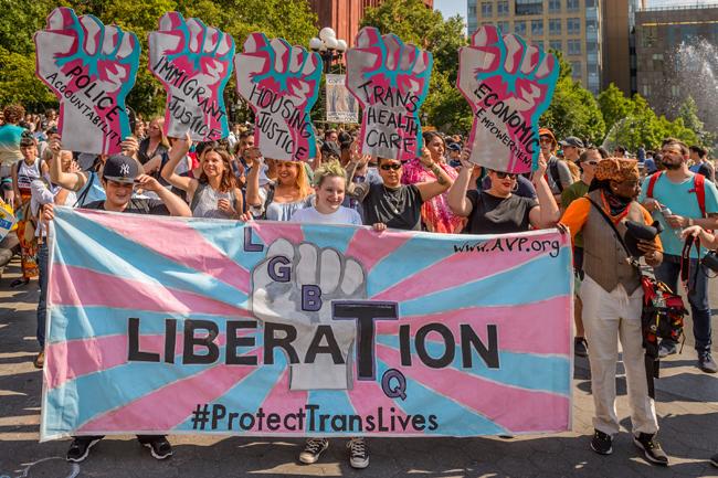 Un grupo de personas se para detrás de una pancarta en el 12 ° Día Anual de Trans, 2016.