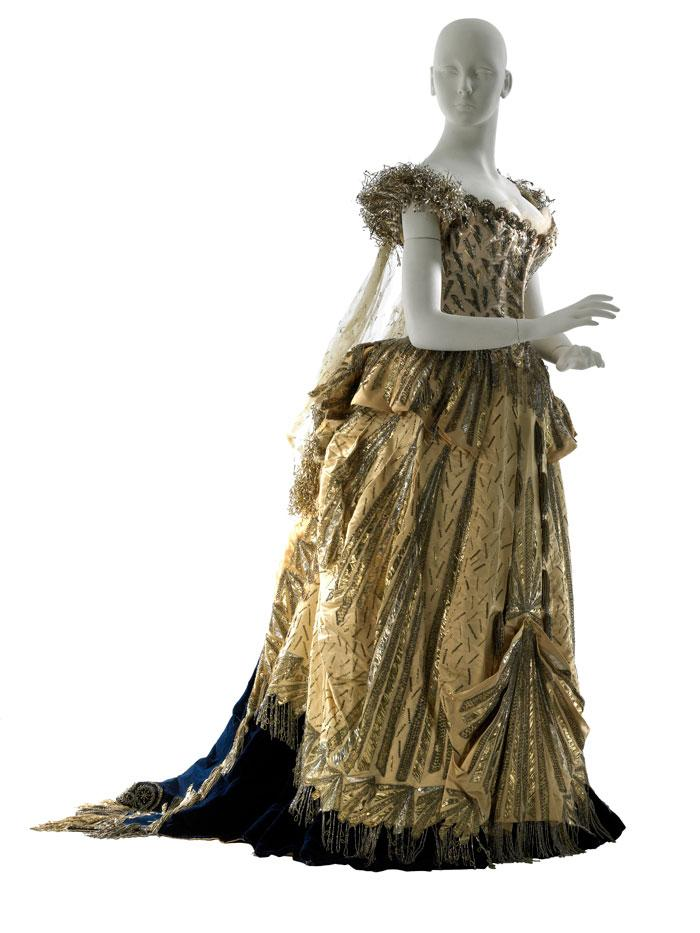 A gold floor-length dress with metallic details, a black underskirt, and blue train