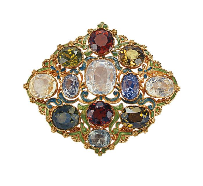 Brooch made of metal, painted green and teal with gold pieces and edges. A number of large gemstones are set in the metal