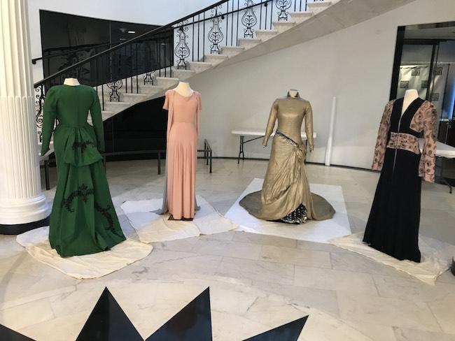 Cuatro vestidos que pertenecieron a Marian Anderson, en varios colores y estilos vestidos con maniquíes colocados frente a la escalera principal del Museo.