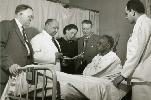 Black and white photograph of Dr. Lyndon M. Hill, Dr. Louis T. Wright, Dr. Myra Logan, Dr. Aaron Prigot, and unidentified hospital employee standing around the bedside of an unidentified African American woman patient.