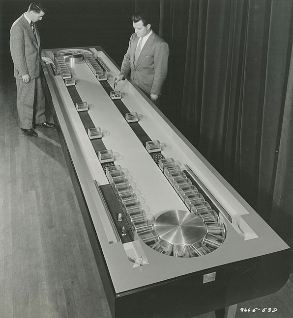 コンベア地下鉄システムの作業モデルを調べるスーツを着た2人の男性。