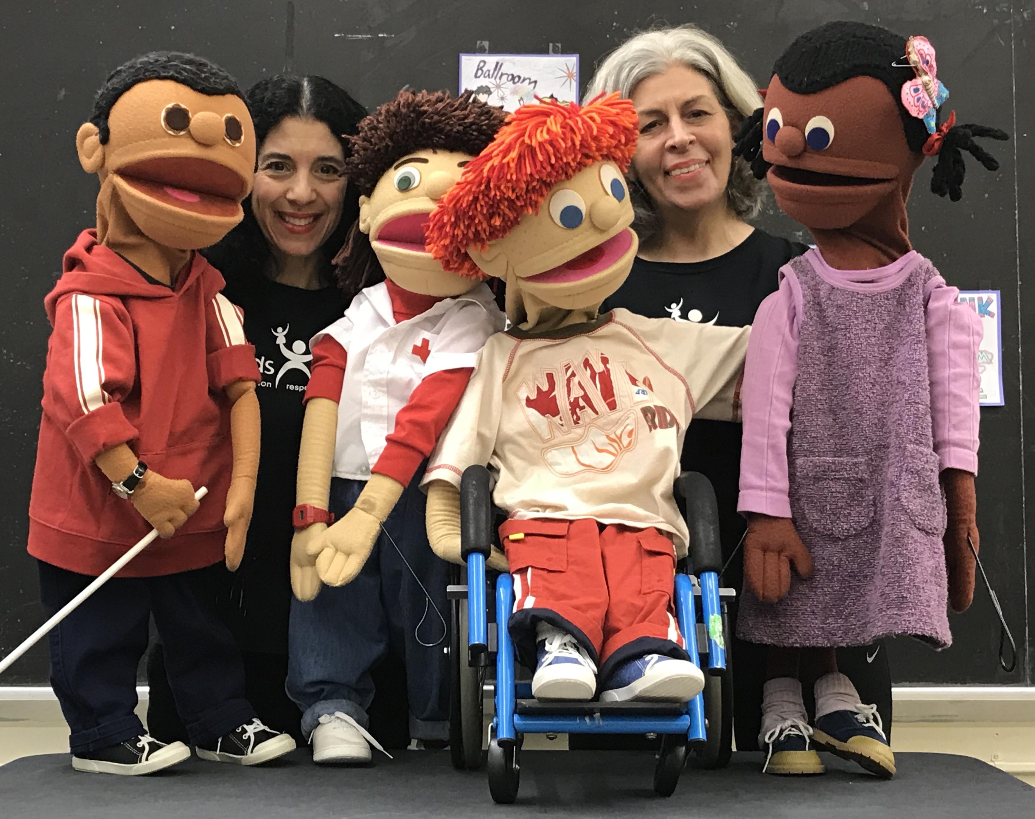 """Un grupo de dos mujeres adultas y cuatro títeres de """"niños"""". Una marioneta está en una silla de ruedas, tres están de pie."""